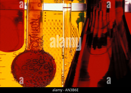 Close up scientific still life of flasks and beakers with dye indicators - Stock Photo