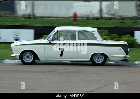 Sir Stirling Moss Racing a Lotus Cortina Mk1 at Goodwood Revival Sussex England UK - Stock Photo