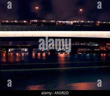 Buses waiting on London Bridge at night, UK - Stock Photo