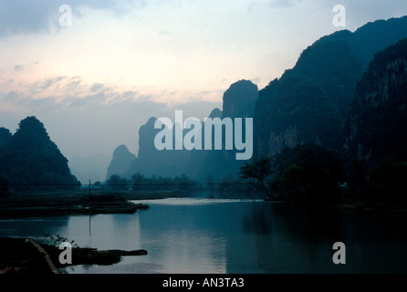 Li River near Fuli China with misty dark karst mountains looming along its banks - Stock Photo