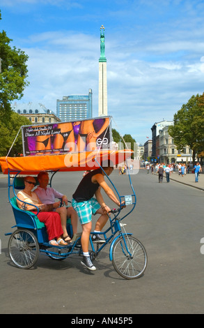 A couple on a velo taxi driver in front of Monument of Freedom in central RIGA capital of Latvia in northern Europe - Stock Photo