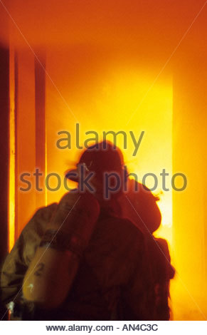 Firefighters are illuminated by heavy flames inside a burning house as they advance a hose line. - Stock Photo