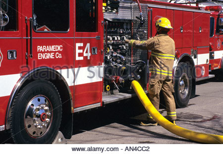 A fire Engineer regulates the flow of water to hoses during a fire from a fire engine's pump panel. - Stock Photo