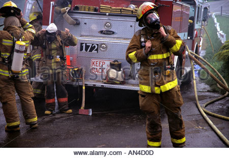 Firefighters regroup by an engine during a fire training drill. - Stock Photo