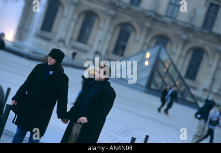 A couple at the courtyard of the Louvre Museum in Paris with the Louvre Pyramid visible in the background - Stock Photo