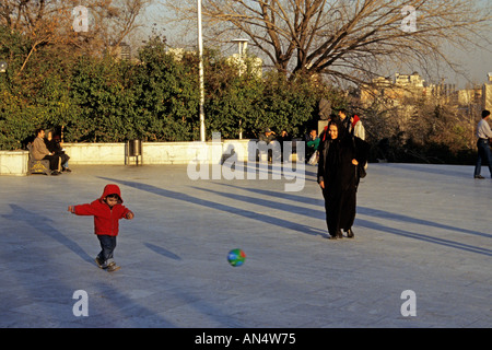 Mother watching son play ball in park, Tehran, Iran - Stock Photo