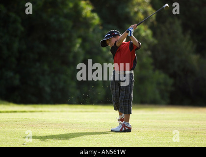 young boy playing golf - Stock Photo