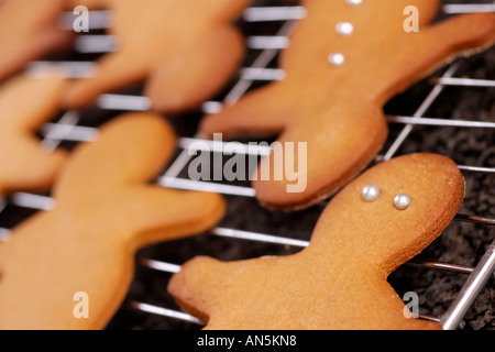 Gingerbread men cooling on wire rack on graite work surface - Stock Photo