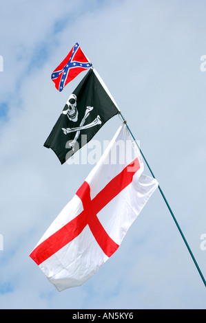 Three flags flying on a single flag pole against a blue cloudy sky flag of St George Jolly Roger and the confederate - Stock Photo