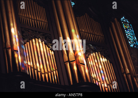 Colours from the stained glass windows in Birmingham cathedral fall on the organ pipes as sun shines through. - Stock Photo
