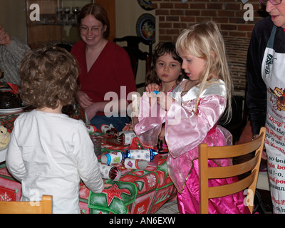 Children with Crackers at the Christmas Dinner Table Child Opening a Present from the Cracker - Stock Photo