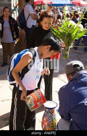 MEXICO Guanajuato Young boy pouring water into vase for flowers Day of the Dead celebration in cemetery - Stock Photo