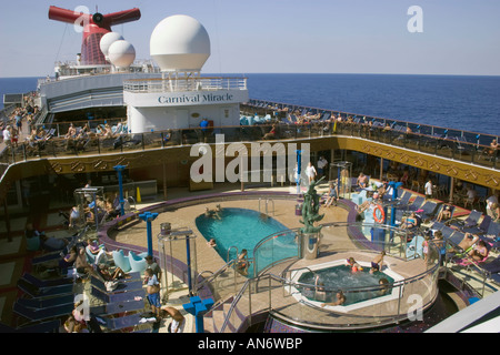 People relaxing by the Lido deck pools on the Carnival Miracle cruse ship - Stock Photo