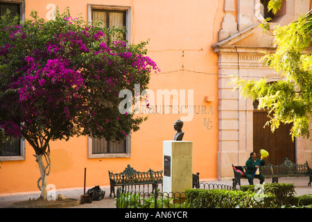 MEXICO Guanajuato Cleaning woman with broom sitting on bench in plaza trees in Jardin Reforma bust of man architecture - Stock Photo