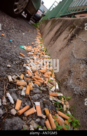CIGARETTE STUBS LYING IN THE GUTTER IN AN URBAN LOCATION UK - Stock Photo