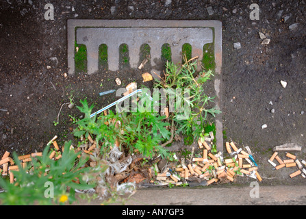 CIGARETTE STUBS LYING IN A GUTTER WITH A BLOCKED DRAIN IN AN URBAN LOCATION UK - Stock Photo