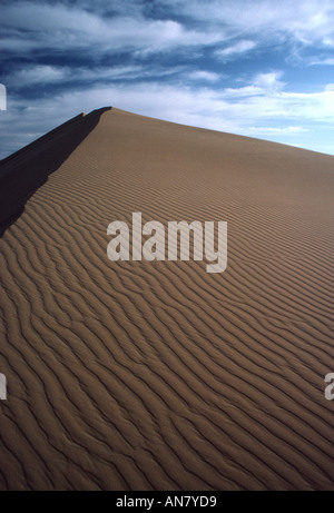 A graphic photograph of wave like patterns on a sand dune in the desert outside Oman set against a blue sky dotted - Stock Photo