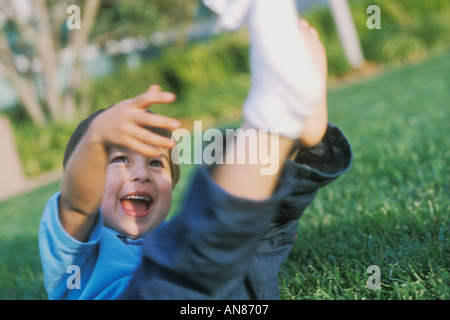 3 year old mixed Caucasian Hispanic Asian boy with his feet in the air on grass - Stock Photo