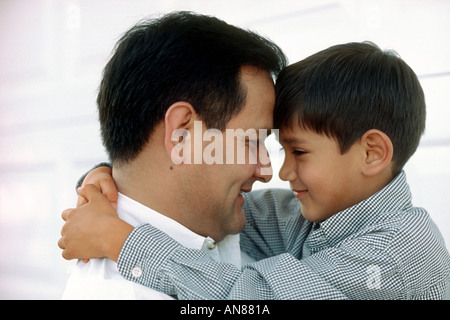 Portrait of 6 year old Mexican American boy hugging his 38 year old Mexican American father - Stock Photo