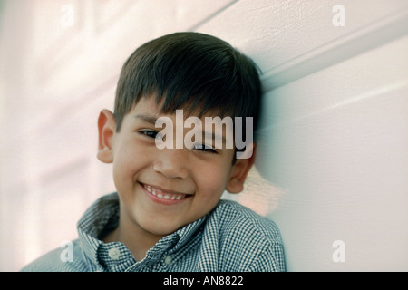 Portrait of 6 year old Mexican American leaning against white wall - Stock Photo