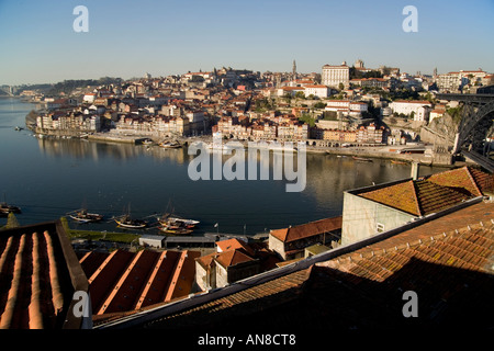 PORTO PORTUGAL Ancient looking boat with empty casks of port wine advertises port wine tasting lodges on bank of - Stock Photo