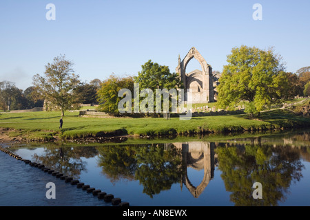 River Wharfe reflecting Bolton Abbey Augustinian Priory ruins in Yorkshire Dales National Park. Wharfedale Yorkshire - Stock Photo