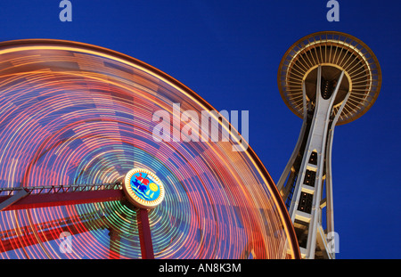 Space Needle and Ferris wheel in Seattle's Pacific Science Center - Stock Photo