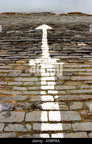 Directional signs paint on rock floor paved outdoor with arrows pointing in opposite directions to the sea - Stock Photo