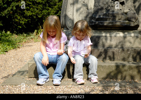 Two girls sitting on statue step. - Stock Photo