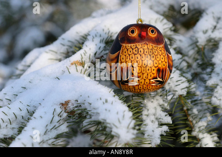 Close up of painted gourd owl ornament hanging on snow covered Christmas spruce tree outdoors in sun - Stock Photo