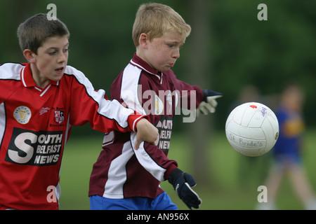 two belfast schoolboys playing gaelic football - Stock Photo