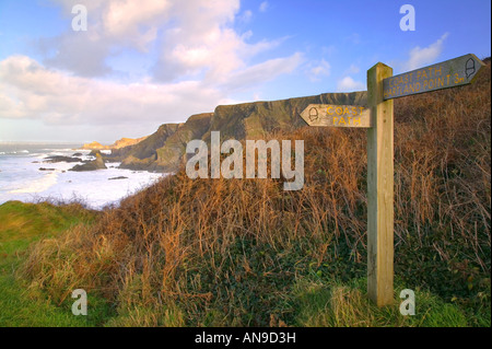 Signpost for the South West Coast Path at Hartland Devon England with views of the cliffs - Stock Photo