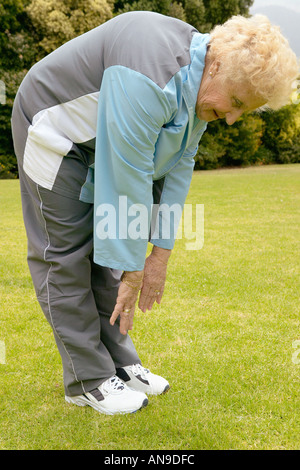 An Old Woman Is Bent Over On A Rural Road Stock Photo