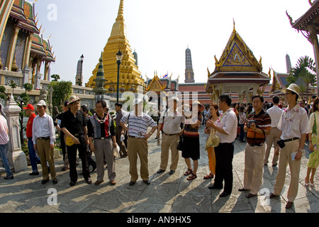 Tourists visit the Grand Palace Complex in Bangkok Thailand - Stock Photo