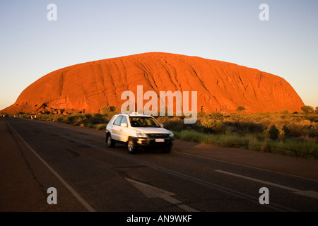 Car drives past Ayers Rock Uluru Red Centre Australia - Stock Photo