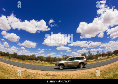 Four wheel drive vehicle on road in the Red Centre Northern Territory Australia - Stock Photo