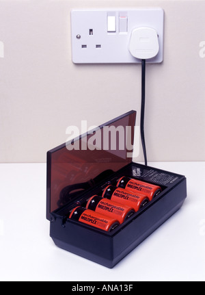 Battery charger charging four D size rechargeable cells - Stock Photo