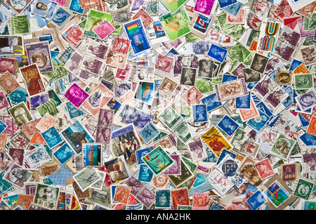 Large assortment of colorful overlapping stamps from many countries - Stock Photo