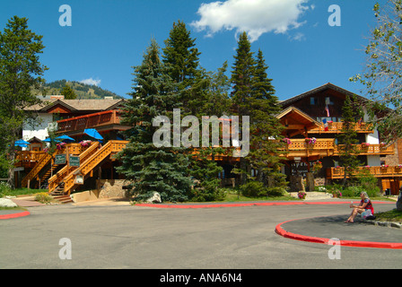 Young Woman Sits Outside The Balconied Chalet Style Alpenhof Hotel in Teton Village near Grand Teton National Park - Stock Photo