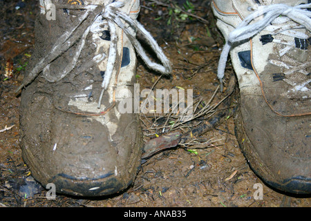 muddy and worn sneakers after a hike in New Zealand - Stock Photo