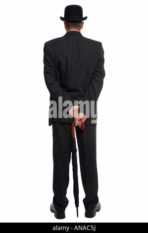 Rear view of a man dressed in a pinstripe suit wearing a bowler hat and carrying an umbrella - Stock Photo