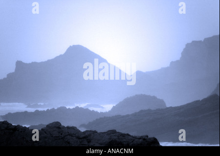 Sea fog on a rocky coastline grainy image as a result of natural light conditions - Stock Photo