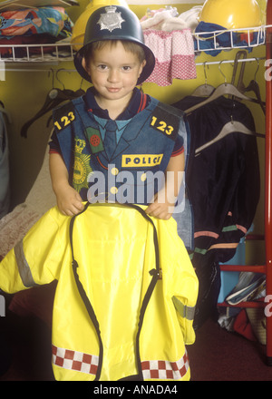 Young boy at preschool dressed in a police outfit playing with dressing up clothes - Stock Photo