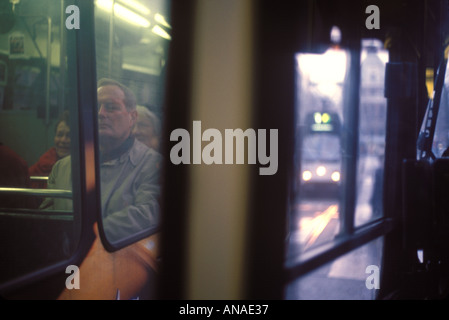 A deceptive view of one tram from inside another tram in Amsterdam with a third tram trailing in the distance For - Stock Photo