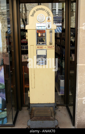 Old fashioned coin operated public weighing machine outside a chemist in Bayeux Normandy France - Stock Photo