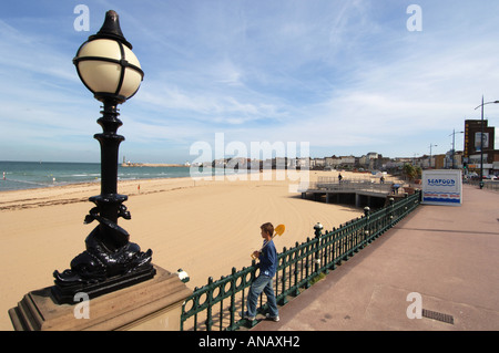 A young boy with a yellow spade alone on the seafront at Margate Kent - Stock Photo