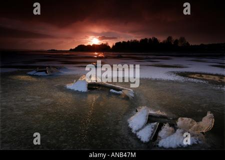 Cracked ice and sunset in Kurefjorden nature reserve, Rygge kommune, Østfold fylke, Norway. - Stock Photo