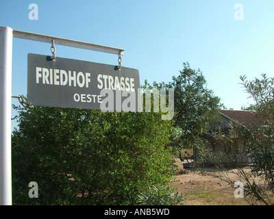 Street sign in mixed German and Spanish language in front of a house of the pioneer's time, Mennonite colony, Filadelfia - Stock Photo