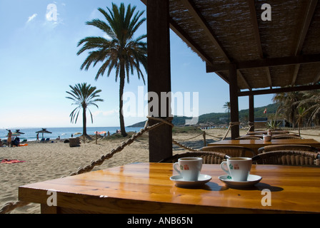 Coffee cups on a wooden table in a beach cafe, overlooking the beach and palm trees on Platja d'en Bossa, Ibiza - Stock Photo