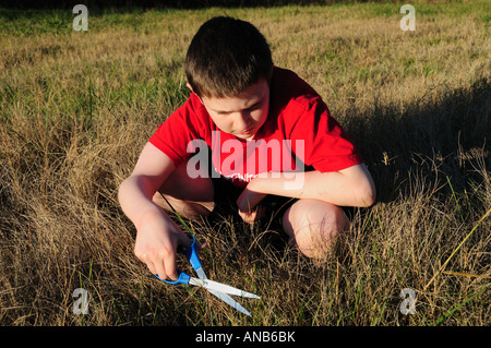 A young boy cuts the grass the slow way one blade at a time. Symbolizes the concept of hard detail at work or a - Stock Photo